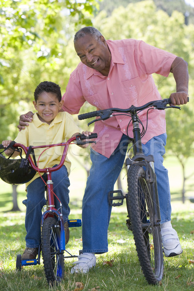Grandfather and grandson on bikes outdoors smiling Stock photo © monkey_business