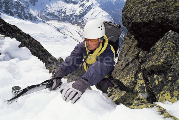 Mountaineer using an ice axe to climb a steep slope Stock photo © monkey_business