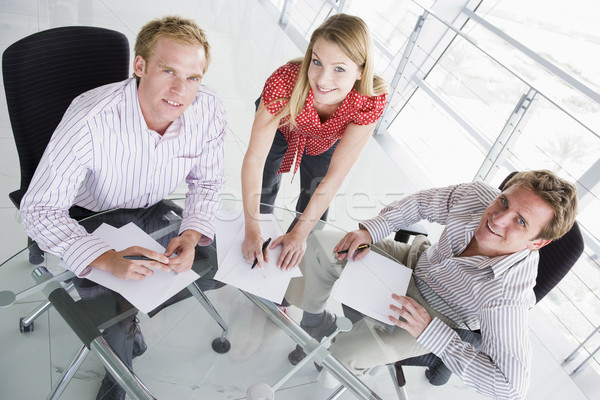 Three businesspeople in a boardroom with paperwork smiling Stock photo © monkey_business