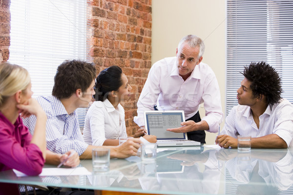 Five businesspeople in boardroom with laptop Stock photo © monkey_business
