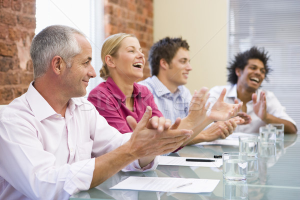 Stock photo: Four businesspeople in boardroom applauding and smiling