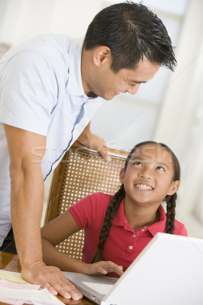Man and young girl with laptop in dining room smiling Stock photo © monkey_business