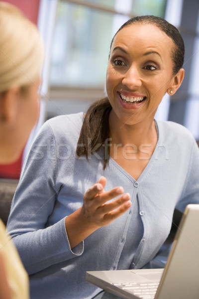 Two businesswomen in boardroom with laptop talking Stock photo © monkey_business