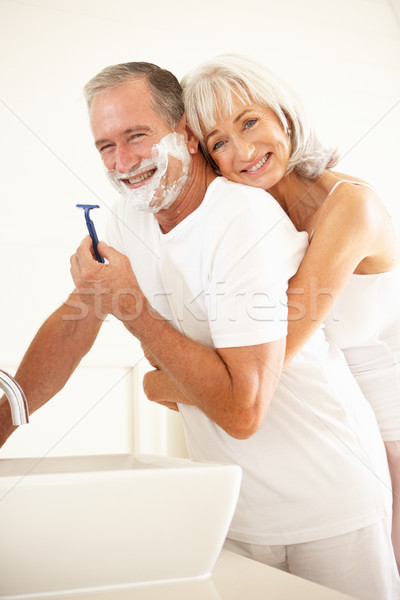 Senior Man Shaving In Bathroom Mirror With Wife Watching Stock photo © monkey_business