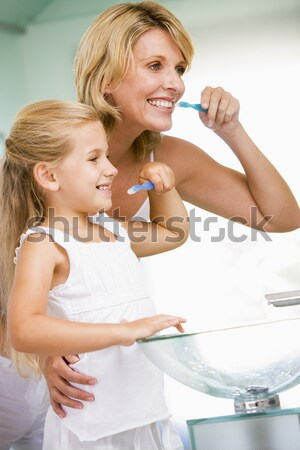 Mother And Daughter Brushing Teeth In Bathroom Together Stock photo © monkey_business