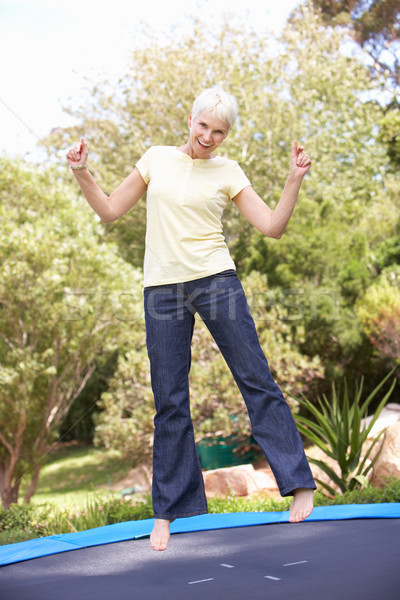 Senior Woman Jumping On Trampoline In Garden Stock photo © monkey_business