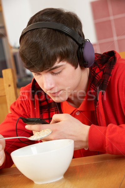 Teenage Boy Listening To MP3 Player Whilst Eating Breakfast Stock photo © monkey_business