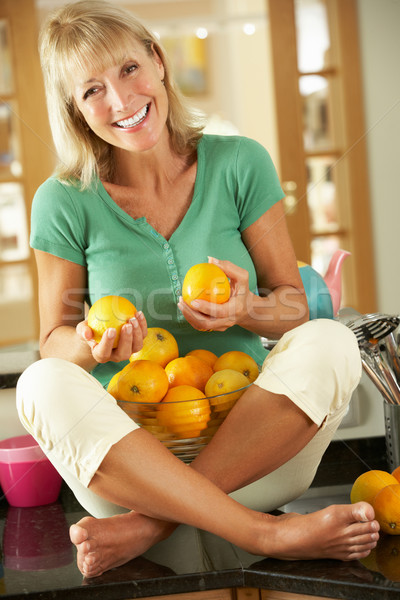 Senior Woman Sitting On Kitchen Counter With Bowl Of Oranges Stock photo © monkey_business