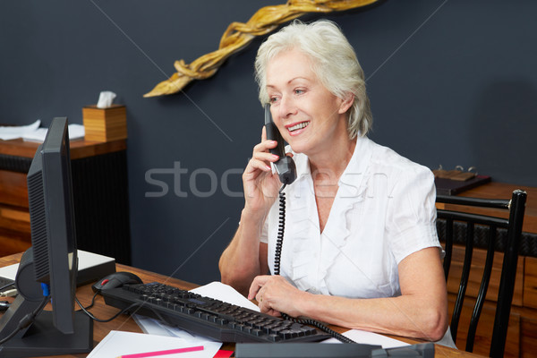 Hotel Receptionist Using Computer And Phone Stock photo © monkey_business