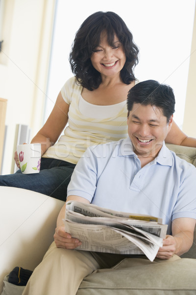 Couple relaxing with a newspaper and smiling Stock photo © monkey_business
