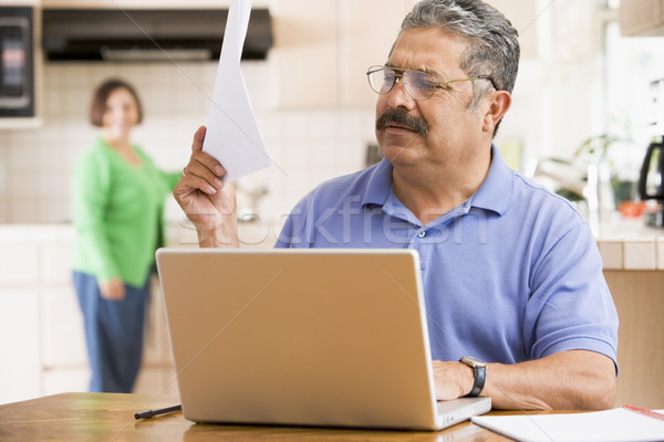 Man in kitchen with laptop and paperwork with woman in backgroun Stock photo © monkey_business