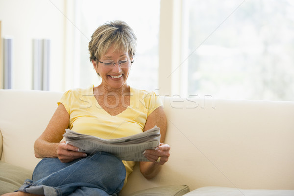 Woman relaxing with newspaper in living room smiling Stock photo © monkey_business