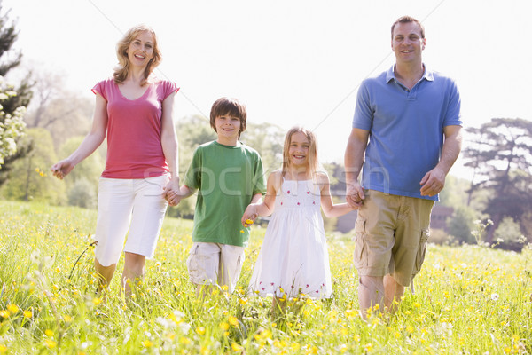 Family walking outdoors holding flower smiling Stock photo © monkey_business