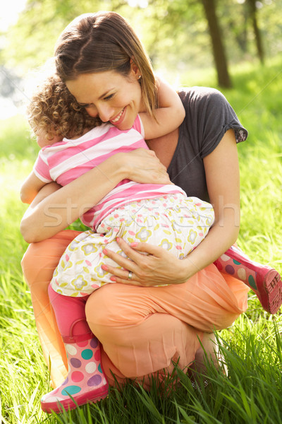 Mother Cuddling Young Daughter In Summer Field Stock photo © monkey_business