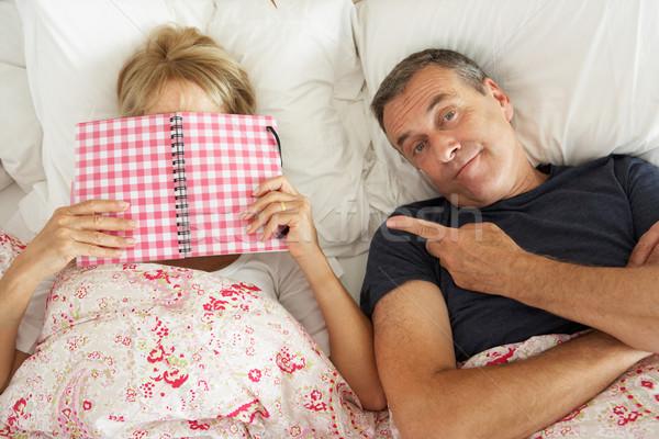 Stock photo: Bored Looking Senior Man Lying In Bed Next To Senior Woman Readi