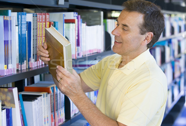 Man in a library reading book cover Stock photo © monkey_business
