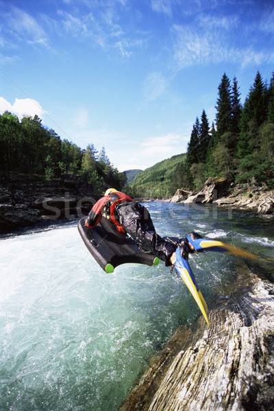 Young woman in wetsuit jumping from cliff into river Stock photo © monkey_business