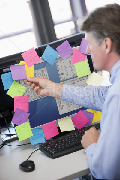 Businessman in office at monitor with notes on it Stock photo © monkey_business