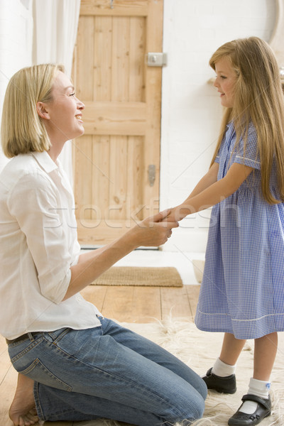 Woman in front hallway holding young girl's hands and smiling Stock photo © monkey_business