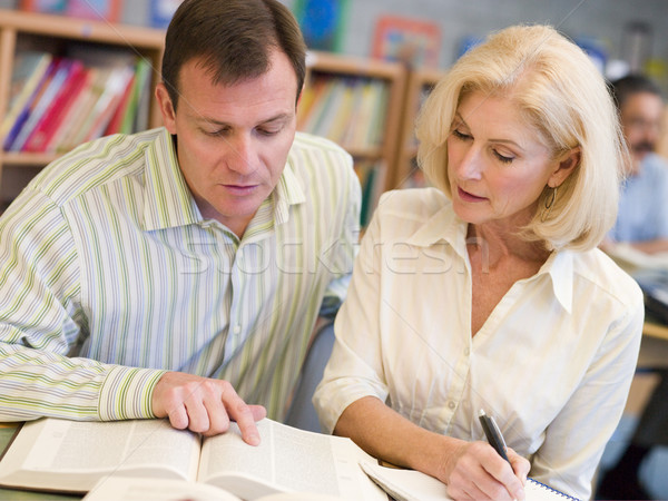 Tutor assisting mature student in library Stock photo © monkey_business