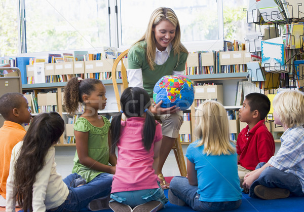 Kindergarten teacher and children looking at globe in library Stock photo © monkey_business