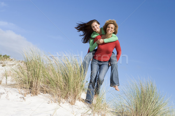 Two friends having piggy back at beach Stock photo © monkey_business