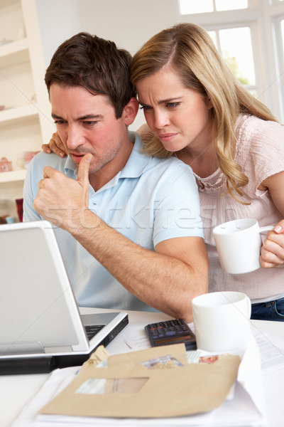 Young couple thinking and looking at a laptop computer Stock photo © monkey_business