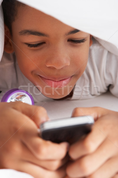 Boy Using Mobile Phone Under Duvet Stock photo © monkey_business