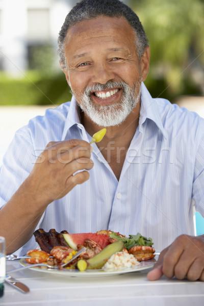 Középkorú férfi ebéd freskó kert asztal tányér Stock fotó © monkey_business