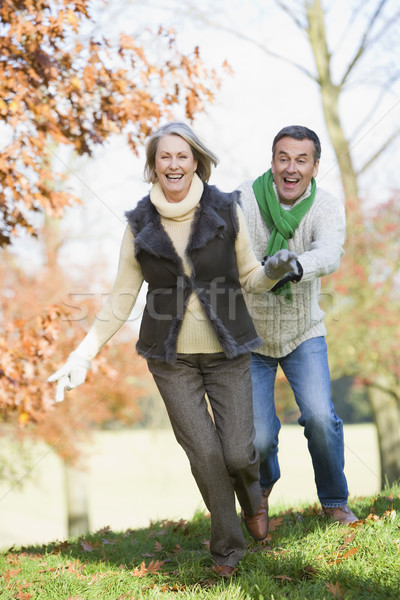 Senior man chasing woman through countryside Stock photo © monkey_business