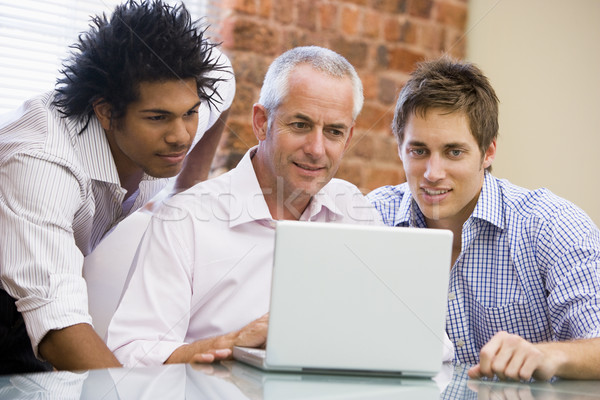 Three businessmen in office looking at laptop smiling Stock photo © monkey_business