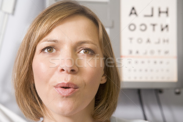 Woman in optometrist's exam room taking deep breath Stock photo © monkey_business