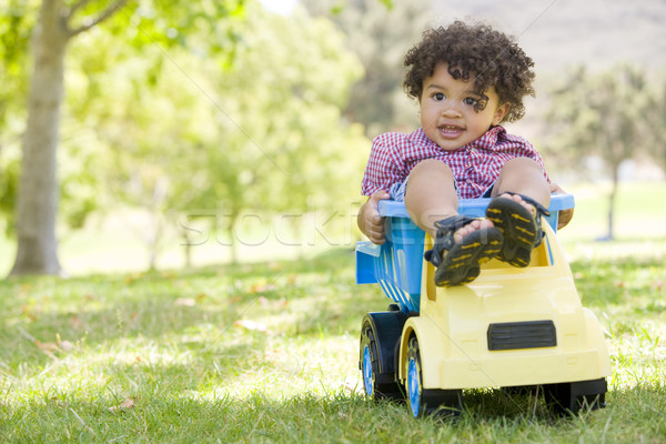 Young boy outdoors playing on toy dump truck smiling Stock photo © monkey_business