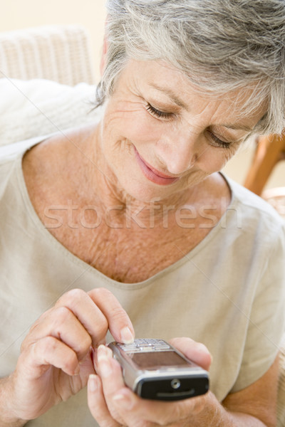 Woman using cellular phone indoors smiling Stock photo © monkey_business