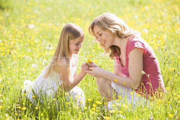 Mother and daughter outdoors holding flower smiling Stock photo © monkey_business