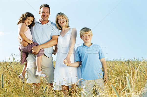 Stock photo: Family standing outdoors holding hands smiling