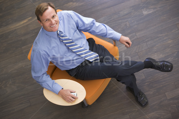 Businessman sitting indoors with cellular phone smiling Stock photo © monkey_business