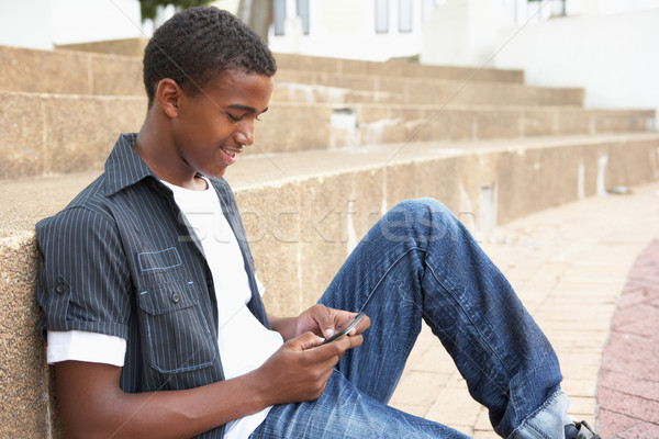Male Teenage Student Sitting Outside On College Steps Using Mobi Stock photo © monkey_business
