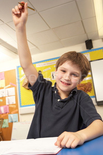 Schoolboy Answering Question In Classroom Stock photo © monkey_business