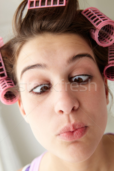 Teenage girl with hair in curlers pulling a face Stock photo © monkey_business