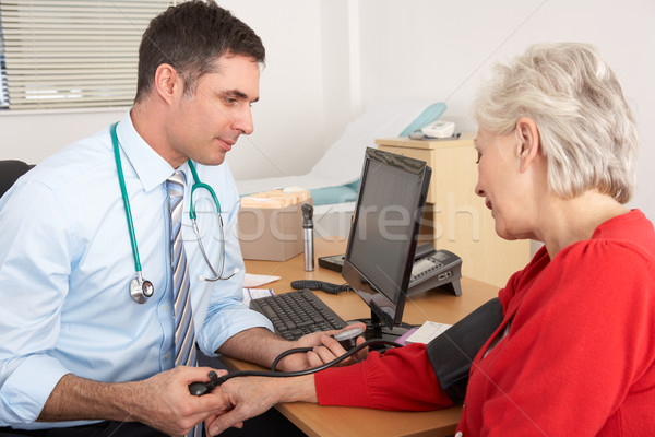 British doctor taking senior woman's blood pressure Stock photo © monkey_business