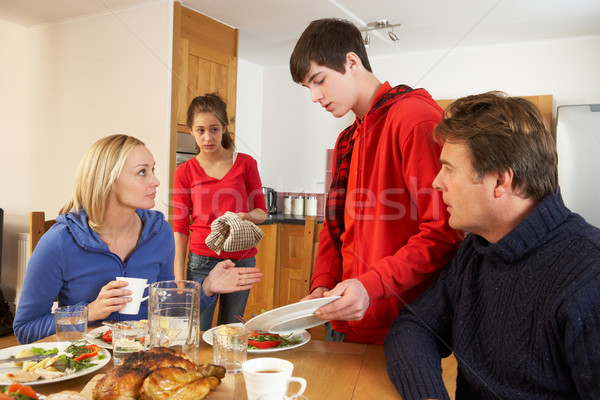 Unhelpful Teenage Clearing Up After  Family Meal In Kitchen Stock photo © monkey_business