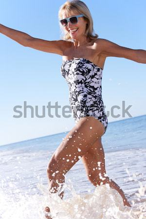 Teenage Girl Wearing Wellington Boots Splashing In Sea On Beach  Stock photo © monkey_business
