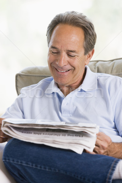 Man relaxing with a newspaper smiling Stock photo © monkey_business