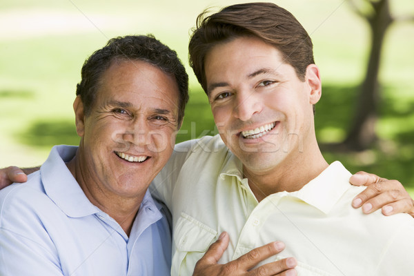 Two men outdoors embracing and smiling Stock photo © monkey_business