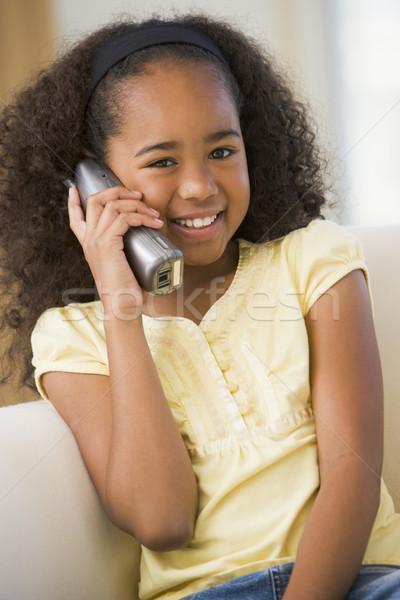 Giovane ragazza seduta divano parlando telefono bambini Foto d'archivio © monkey_business