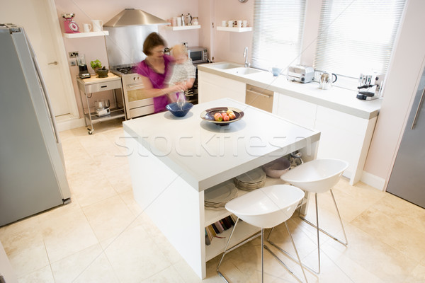Woman in kitchen whisking on counter holding baby Stock photo © monkey_business