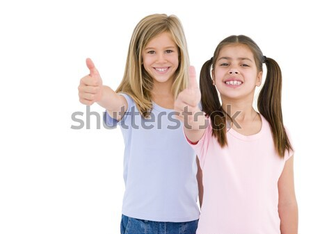 Two girl friends giving thumbs up smiling Stock photo © monkey_business