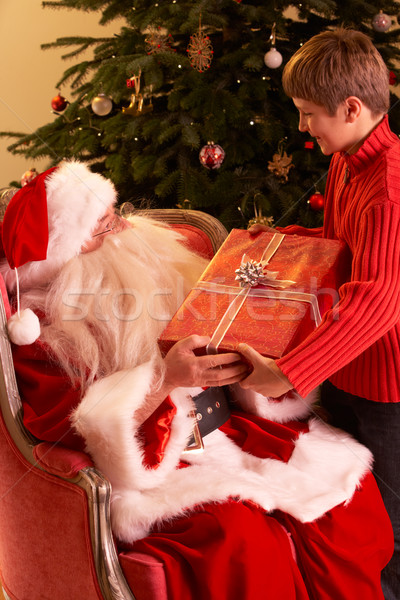Santa Claus Giving Gift To Boy In Front Of Christmas Tree Stock photo © monkey_business