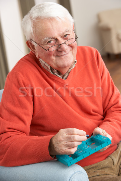 Senior Man Sorting Medication Using Organiser At Home Stock photo © monkey_business